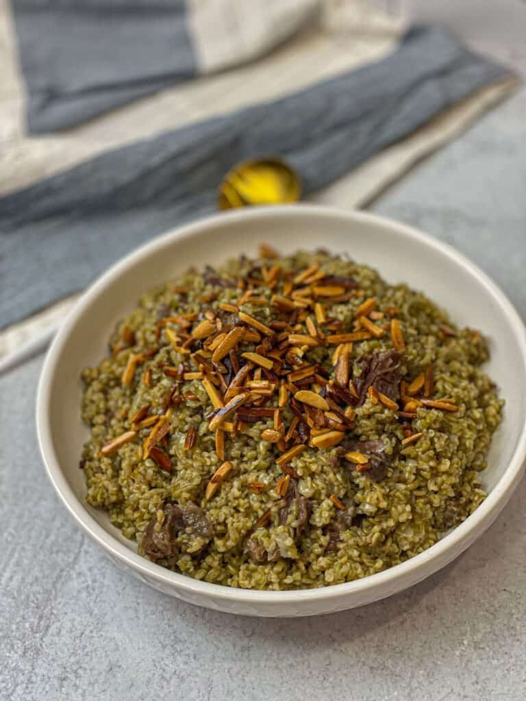 Hearty creamy freekeh with meat and topped with golden nuts