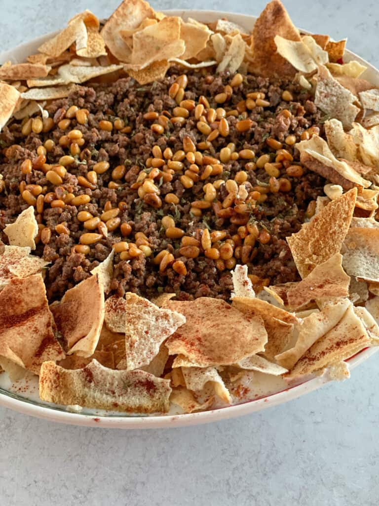 Fattet sujuk or Sujuk Fatteh is the ultimate breakfast dish layered with a tangy delicious yogurt sauce, creamy hummus spread, perfectly cooked chickpeas, ground beef in flavor-packed sujuk spices, crunchy toasted pita chips, and yummy toasted pine nuts!