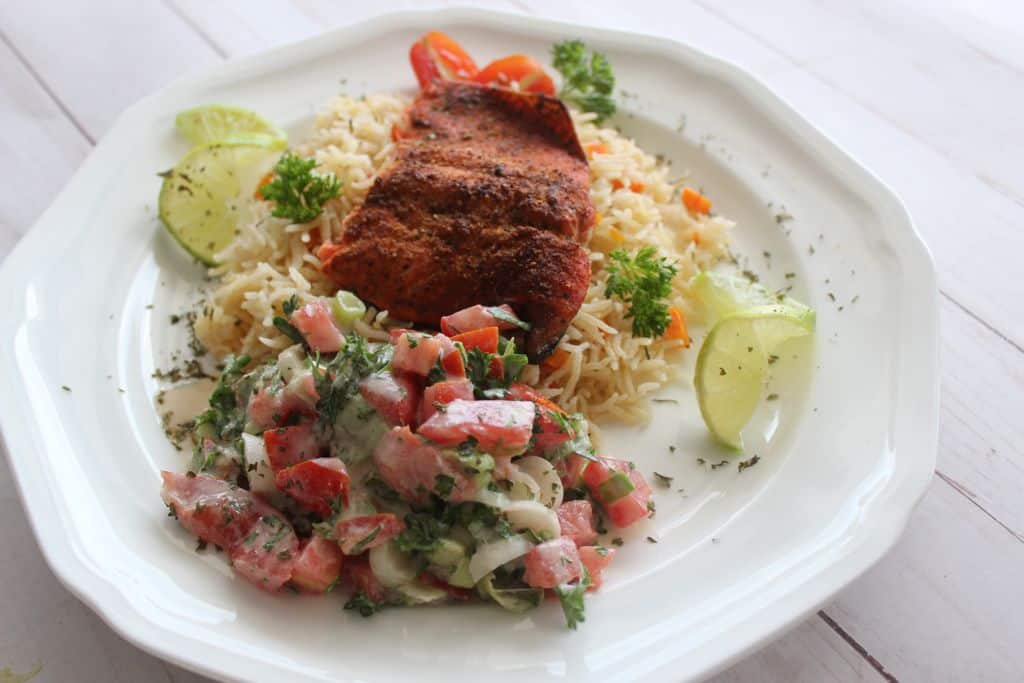 A delectable flakey baked salmon on a bed of Cajun rice with a zesty and tangy side Tahini salad that becomes an irresistible meal!
