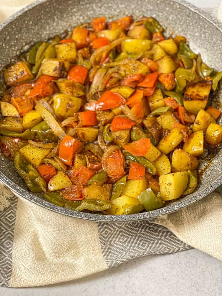 Skillet-Sautéed Potatoes and Onions is a great fried potato, peppers, and onion dish with a juicy tomato base that is packed with flavor!