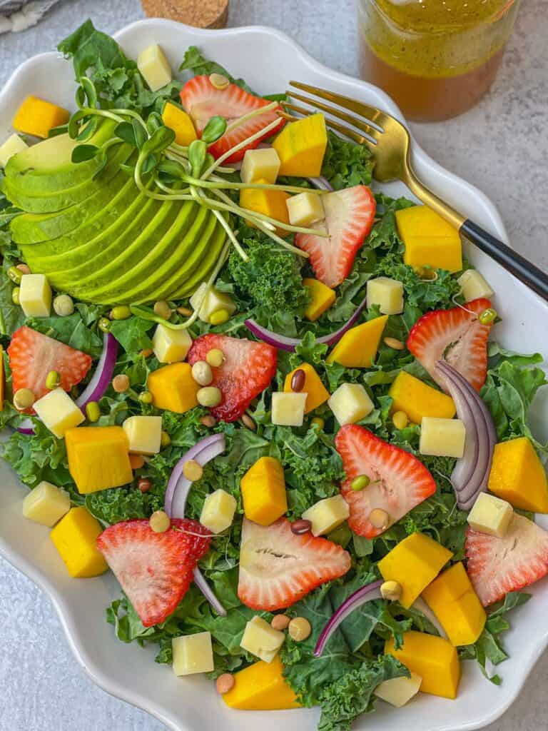 A healthy nutritious and filling salad made with kale, strawberry, mango, red onion, avocado, cheddar cheese, lentil sprouts, and a delicious citrus vinaigrette with oranges. Easy to make and divinely satisfying salad.