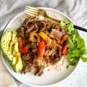 beef steak fajita bowl with peppers, onions, spices, avocados, and rice