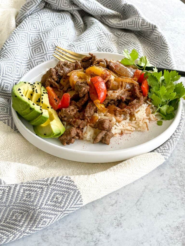 A hearty beef steak fajita bowl with peppers and onions on a bed of white vermicelli rice and a side of avocado