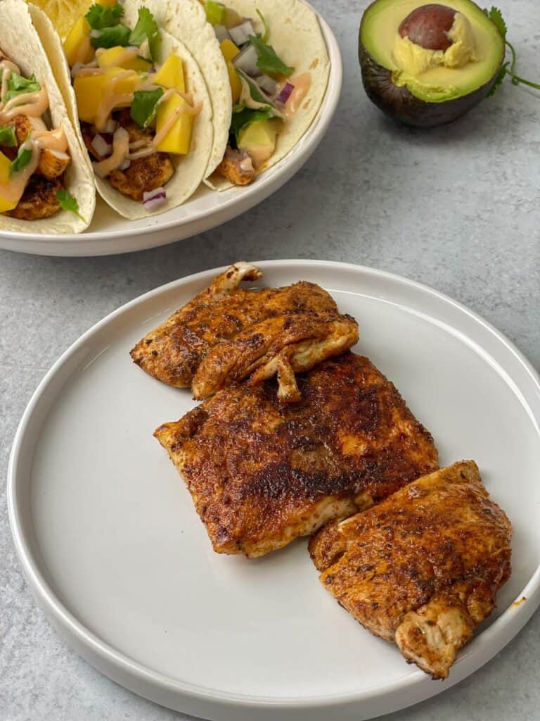 Delicious blackened mahi mahi fish turned into flavor-packed tortilla tacos that are easy and packed with mangoes, avocado, cilantro, and a mahi sauce