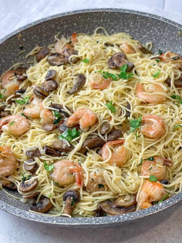 Mushrooms, onions, garlic, shrimp, and pasta come together with some cilantro garnish to make an amazing wine-free and easy shrimp scampi that is delicious