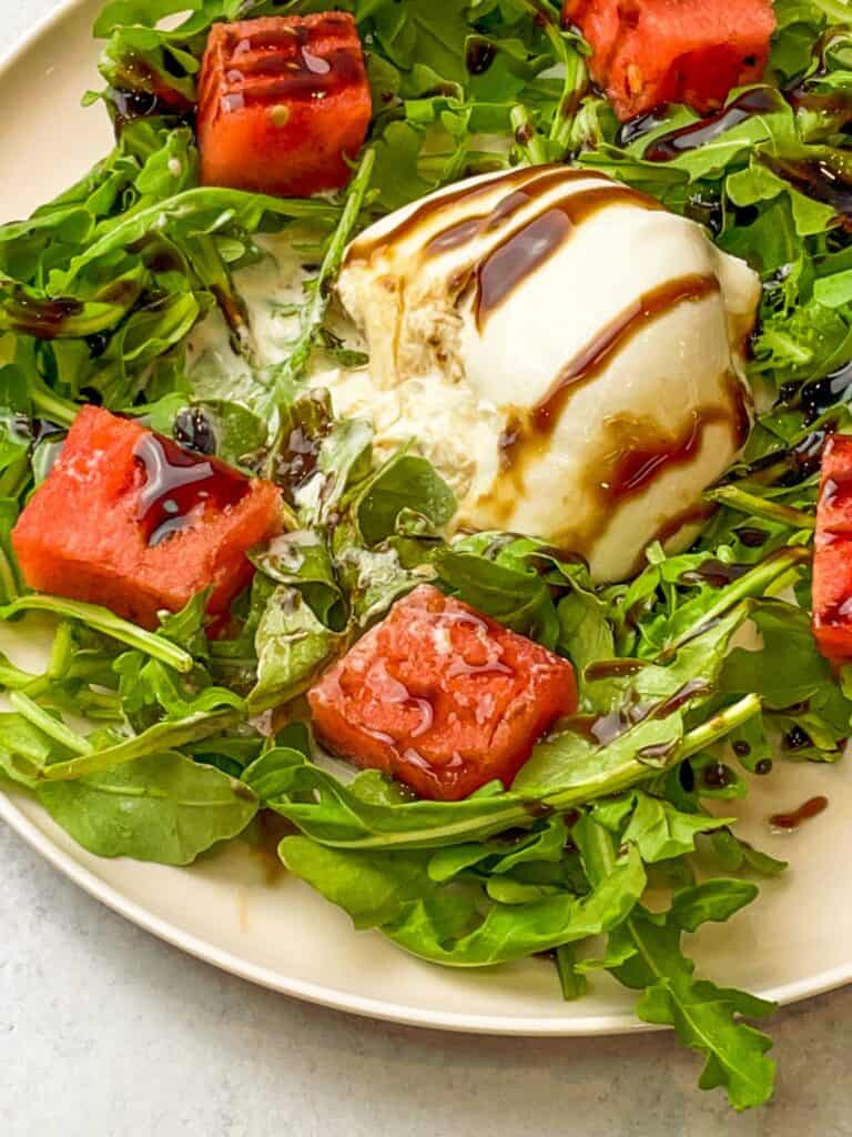 balsamic reduction on a ball of burrata cheese surrounded by a bed of arugula topped with watermelons
