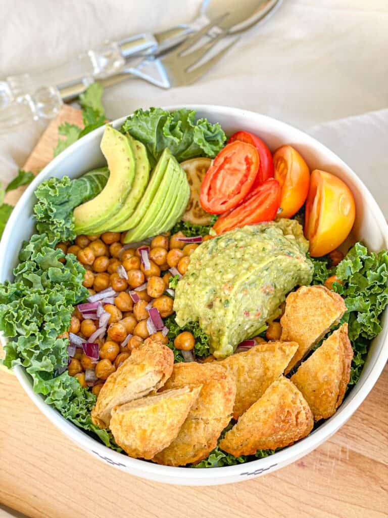This delicious roasted chickpea avocado salad features kale, a variety of yummy veggies, and crunchy roasted chickpeas with a creamy avocado dressing for a mouthwatering combo you'll love.